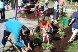 children planting shrubs montessori school